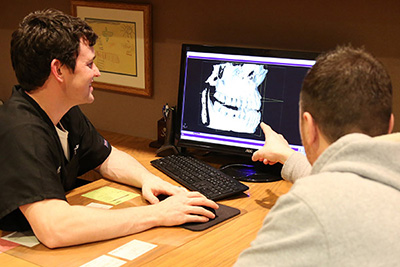 Doctor showing patient xrays on computer screen