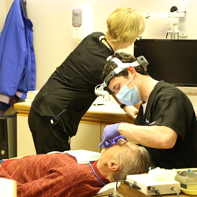 Man getting periodontal therapy in chair